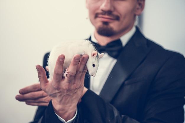 Белая крыса на руках у мужчины в пиджаке