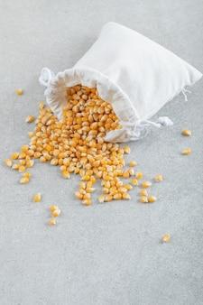 Белый мешок кукурузных зерен на серой поверхности.
