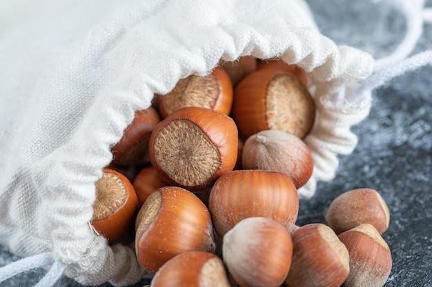 Белый мешок, полный восхитительных орехов макадамия.