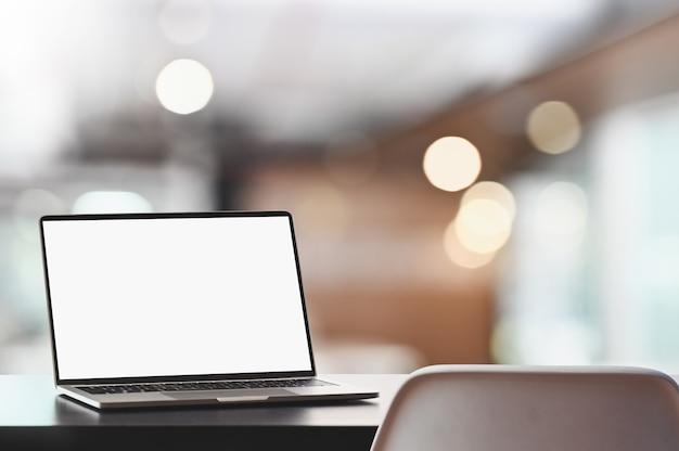 白い画面のラップトップは、ぼやけたオフィス内部の背景を持つ木製の机の上に置いています