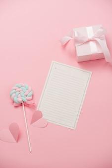 愛する人へのメッセージのための白い紙、ピンクの背景にキャンディー。幸せな女性の日のコンセプト。モックアップ
