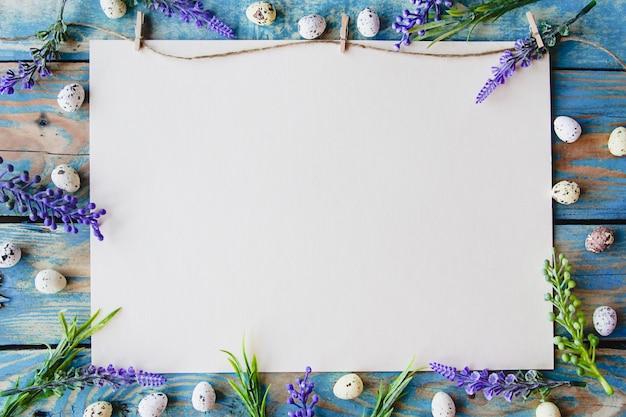 着用した青い木製のテーブルに紫色の花とウズラの卵で囲まれた白い紙