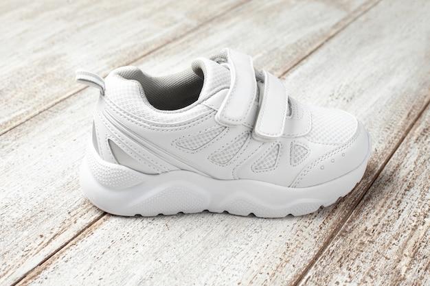 Белые кроссовки на светлом фоне одной детской кожи с тканевыми спортивными кроссовками на липучке ...
