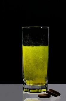 흰색 정제가 물 한 컵에 녹아 검정색 배경에 물이 노란색으로 변합니다.