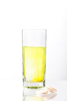 흰색 정제가 물 한 컵에 녹아 물이 노랗게 변합니다.