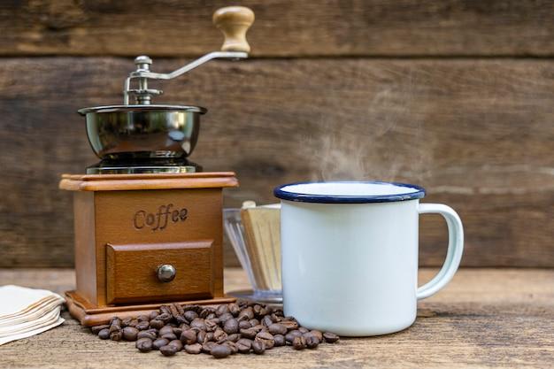 木製のテーブルにコーヒーグラインダーとコーヒー豆とホットコーヒーの白いブリキのカップ。