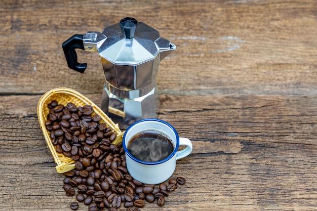 イタリアのコーヒーポット(真岡)と木製のテーブルにコーヒー豆とホットコーヒーの白いブリキのカップ。