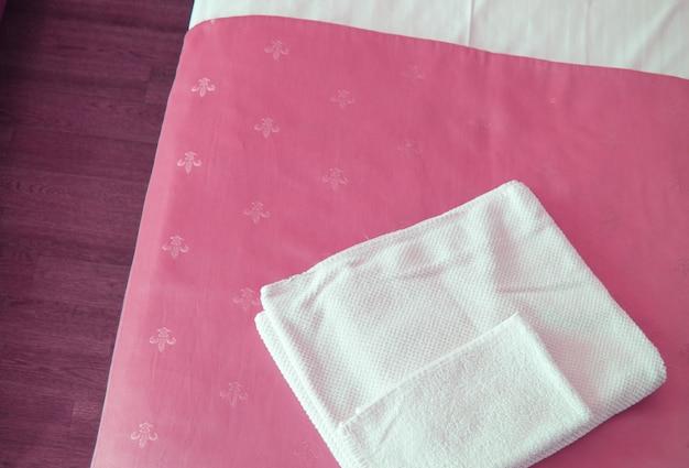 침대 위의 고급스러운 분홍색 침대보에 흰색 수건이 있고 위에서 클로즈업된 모습입니다.