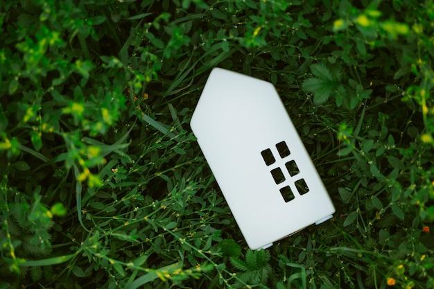 草の中の白いおもちゃの家環境にやさしいライフスタイルのコンセプト