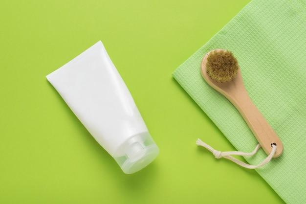 Белый тюбик крема и массажер для лица на зеленом фоне. концепция ухода за телом. спа. плоская планировка.