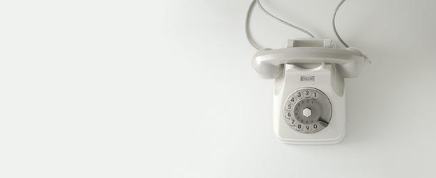 白い背景の白いビンテージダイヤル電話。