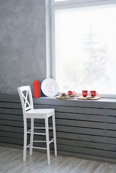 흰색 나무 막대 의자는 크리스마스 빨간 머그잔과 장식이있는 창턱과 창 근처에 서 있습니다.