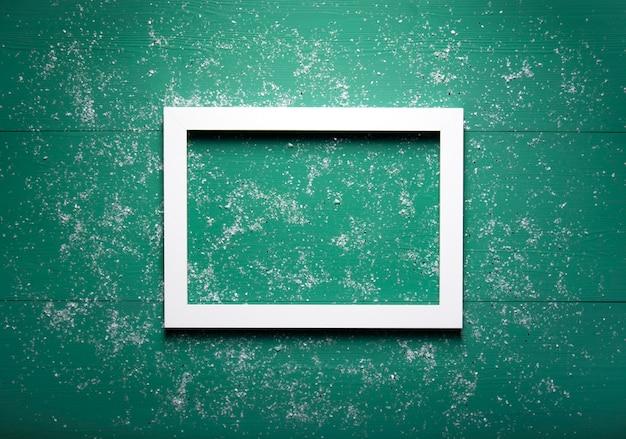 Белая деревянная рамка лежит на зеленом деревянном фоне, усыпанном снегом.