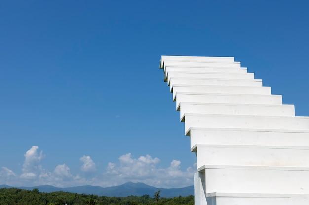 Белая деревянная лестница или лестница, ведущая к голубому небу с ярким живописным горным фоном.