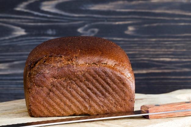 Целая буханка черного хлеба на разделочной доске