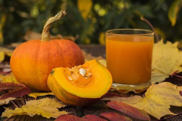 カボチャ全体、カボチャの一部、秋の葉のカボチャジュースのガラス