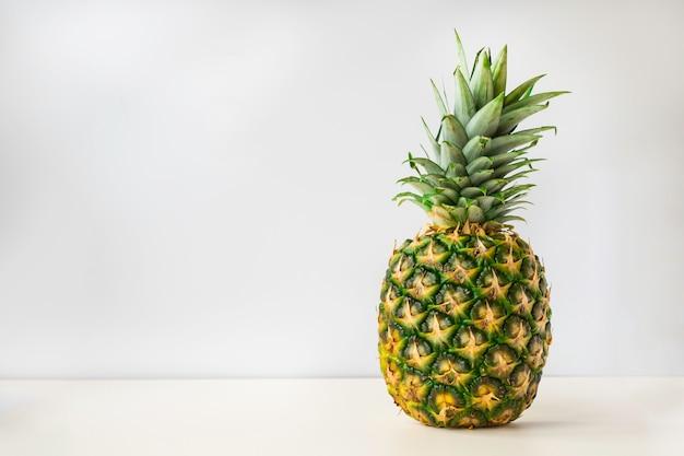 熟したパイナップル全体が白い表面に立つ