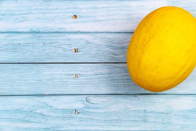 全体の黄色いメロンは青い木製の背景の上にあります。夏のコンセプト。