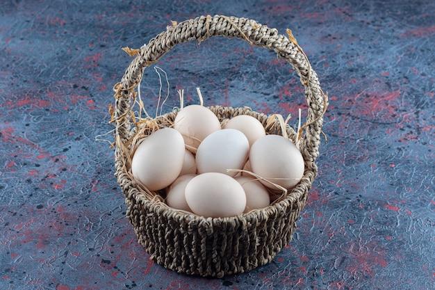 신선한 생 닭고기 달걀로 가득 찬 고리 버들 세공 바구니