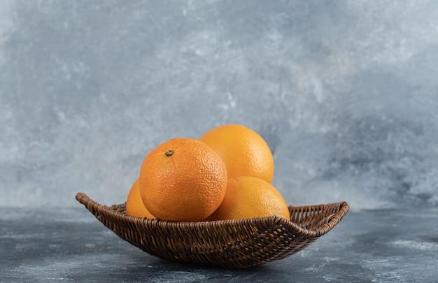 オレンジ色の果物がいっぱい入った籐のバスケット。