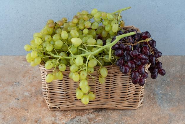 大理石のテーブルに甘いブドウがいっぱい入った籐のバスケット。