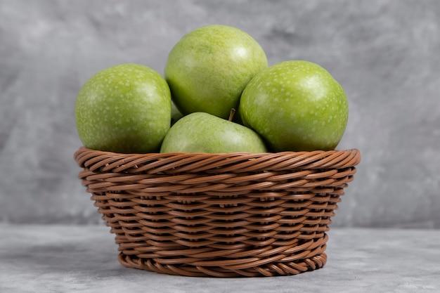 石の上の新鮮な青リンゴの籐のバスケット