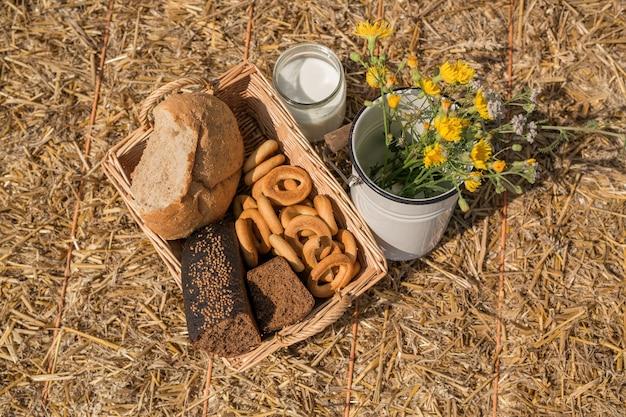 フィールドでのピクニック用のパンと新鮮なミルクの缶が入った籐のバスケット。