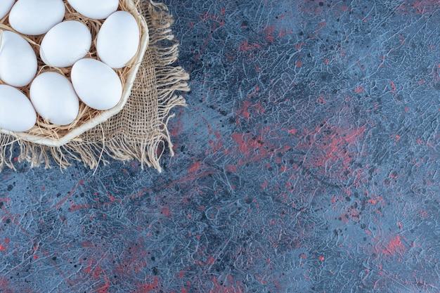 Плетеная корзина со свежими сырыми куриными яйцами