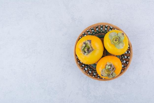 白い背景の上の3つの柿の籐のボウル。高品質の写真