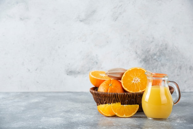 Плетеная коробка, полная сочных апельсиновых фруктов на каменном столе.
