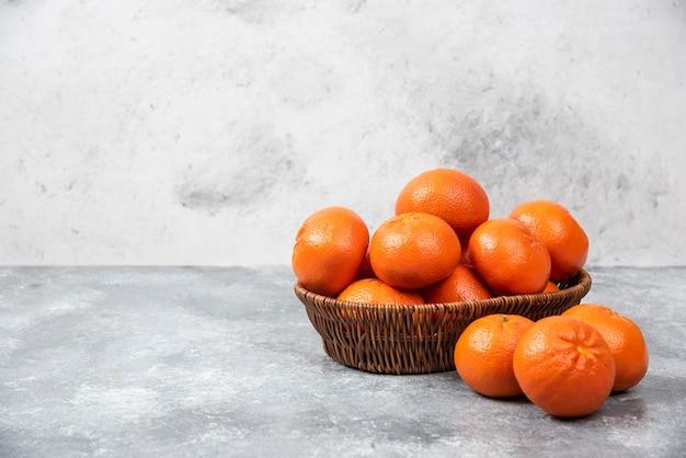 돌 테이블에 수 분이 많은 오렌지 과일의 전체 고리 버들 상자.
