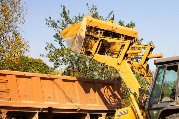 Широкий металлический ковш экскаватора выкапывает песок или глину и загружает их в самосвал на стройке.