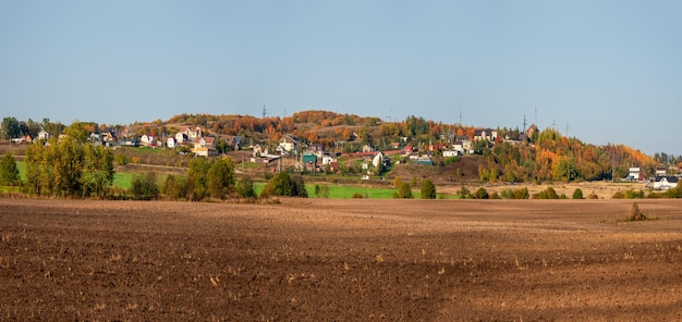 緑の丘の上の村の前にある集団農場の広いパノラマ。