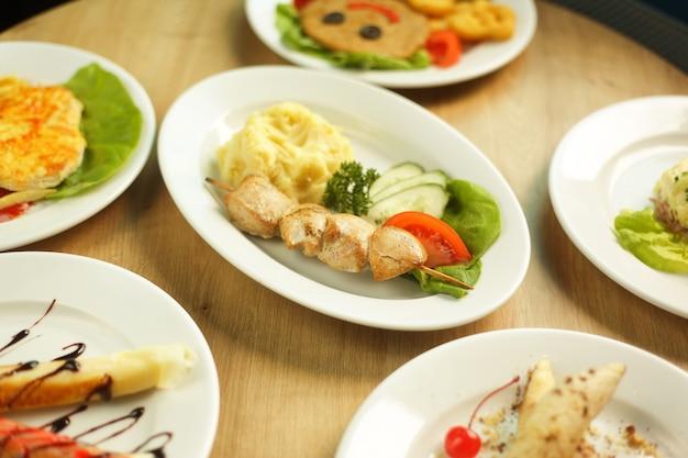 Большой выбор блюд на столе в детском ресторане.