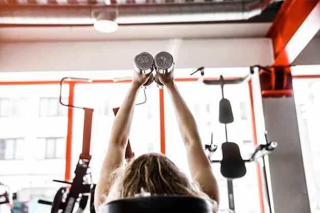 ウィマンは両手を空中に上げてトレーニング器具の上に横たわっています。彼女は2つのダンベルを持っています。