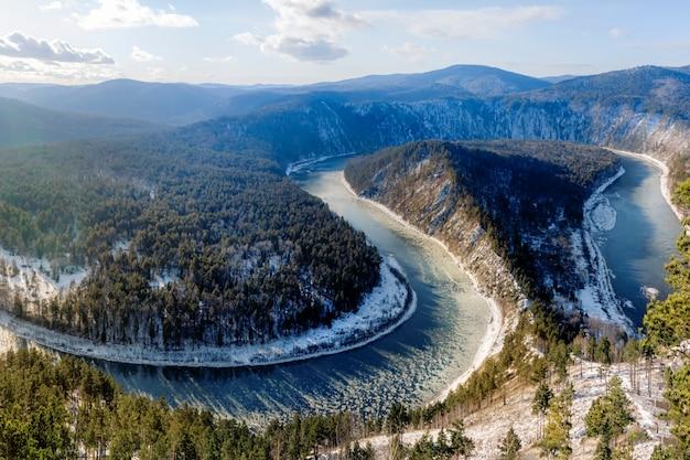 雪に覆われた曲がりくねった川。水は徐々に凍ります