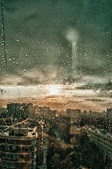 雨滴が街と雲を背景にした窓