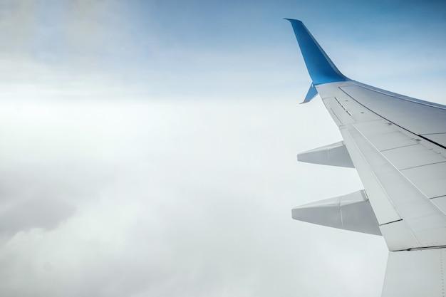 Крыло современного пассажирского самолета над облаками. международные грузоперевозки, авиаперелеты, транспорт. скопируйте пространство.