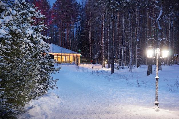 겨울 눈 길은 나무를 지나 빛나는 크리스마스 집으로 이어집니다.