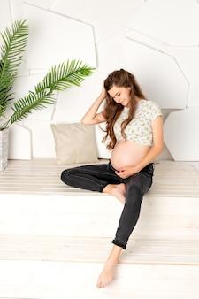 임신 8 ~ 9 개월 된 여성이 밝은 방의 창가에 앉아있다