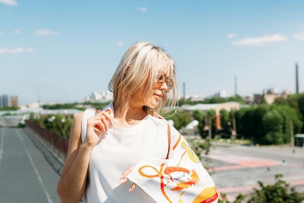 Женщина, девушка в очках и красивом шарфе на крыше дома, ветер и солнце, лето и красота