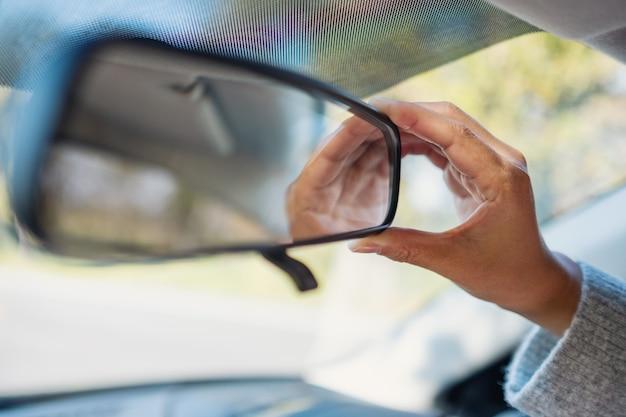 Женщина регулирует зеркало заднего вида во время вождения автомобиля
