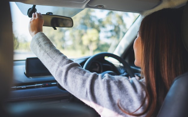 車の運転中にバックミラーを調整する女性