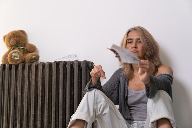 アパートの床に座っている年配の女性が手に持っている紙飛行機を燃やす