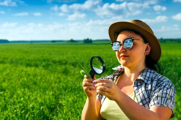 サングラスと帽子をかぶった女性農学者が、虫眼鏡で作物の芽を調べます。横の写真