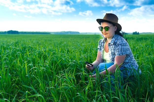畑の女性農学者が虫眼鏡で作物の芽を調べます。横の写真
