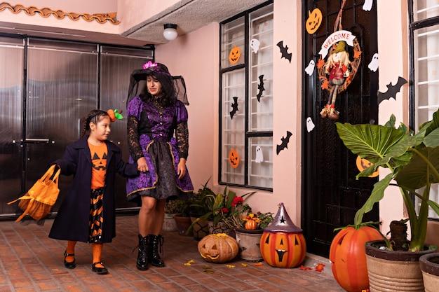 変装した女性と少女がハロウィーンの装飾が施された家のドアをノックしようとしています