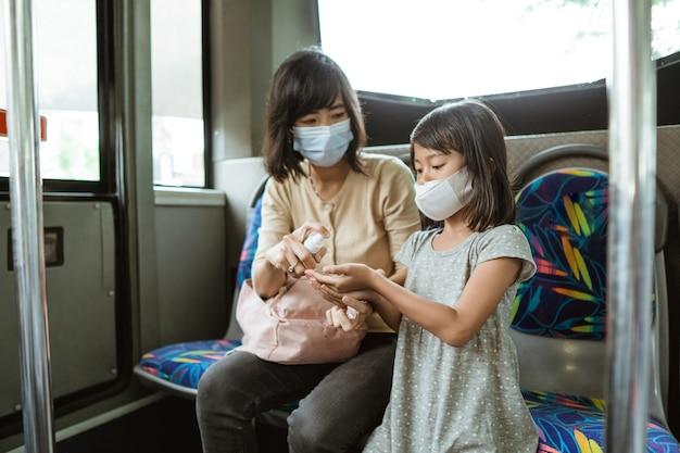 여자와 마스크를 쓰고있는 어린 소녀는 여행하는 동안 버스에서 손 소독제를 사용하여 벤치에 앉아