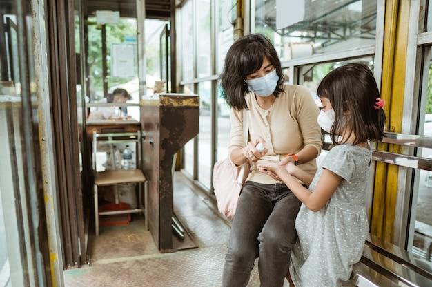 버스 정류장에서 버스를 기다리는 동안 마스크를 쓴 여자와 어린 소녀가 손 소독제를 사용하여 앉아