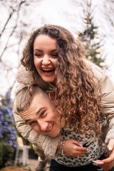 한 여자와 남자가 크리스마스 트리 근처에 서 있고, 그들은 행복하고, 새해 분위기입니다.